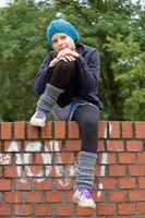 Mädchen sitzt auf einer Mauer