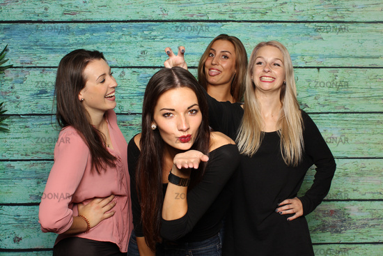 4 pretty girls fool around in front of a photo box