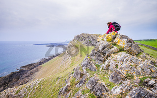 Female Backpacker Looking Into Distance At Rocky Sea Shore In Rhossili, Wales Coast Path