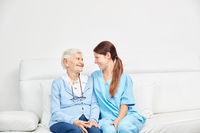 Altenpfleger und Seniorin sitzen auf einer Couch
