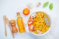 Italian foods concept and menu design . Pasta elbow macaroni  with ingredients sweet basil ,tomato ,garlic ,extra virgin olive oil ,parsley ,bay leaves and champignon  on white background  flat lay .