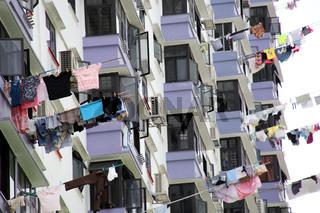 Wohnhochhaus, Wäsche hängt an Stangen zum Trocknen aus dem Fenster