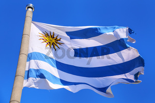 National flag of Uruguay flying in blue sky