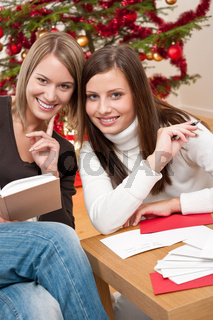 Two young women writing Christmas cards
