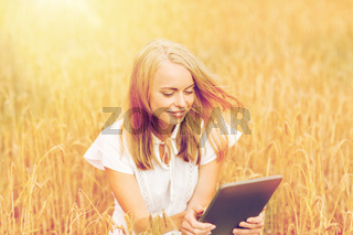 happy young woman with tablet pc on cereal field