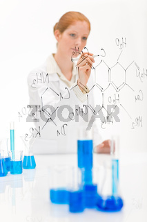 Woman scientist in laboratory write chemical formula