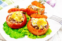 Tomatoes stuffed with meat and rice with lettuce in plate on board