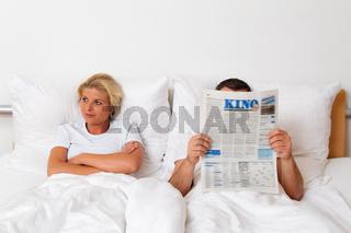 Lesen einer Zeitung im Bett