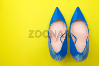 Fashionable blue lacquered shoes on a bright yellow background
