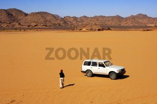 Tourist und Geländewagen inmitten der Sahara