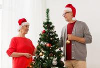 happy senior couple decorating christmas tree