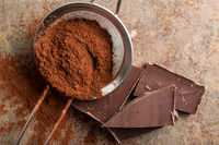 Dark cocoa powder in a sieve and chocolate.
