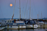 Sailing and motor yachts moored in the harbor in the blue hour at full moon