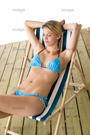 Beach - Young woman in bikini sitting on deck chair relaxing