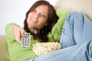 Woman watching television with popcorn in living room