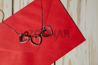 Closeup of silver heart pendants on a red envelope