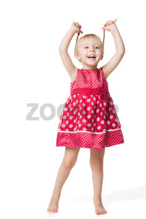 Cute smiling little girl in red dress posing at studio
