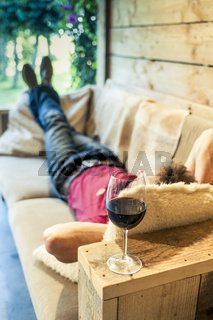 Happy man resting in a couch drinking a cup of red wine
