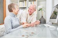 Rentner Paar mit Taschenrechner freut sich