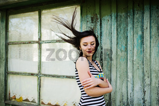 Brunette model girl with hair on the air wearing on dress with stripes background cian wooden house with old windows.