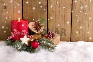 Weihnachten - Päckchen und Kerze vor Holzzaun mit Schneeflocken