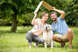 Familie mit Hund hält ein Dach
