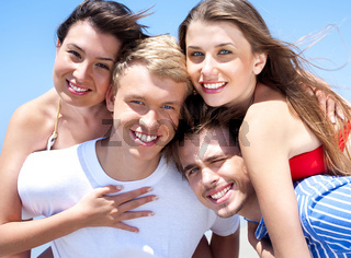 Two Smiling Young man giving piggyback to their girlfriends on holiday. Girls hugging there boyfriend