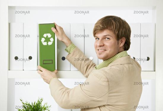Businessman removing green folder from shelf