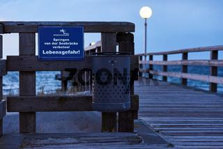 Seebrücke mit Warnschild