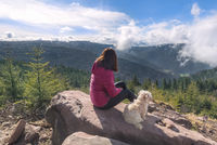Girl and her dog sitting on a rock high up