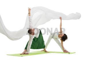 Slim man and woman doing yoga exercises in studio