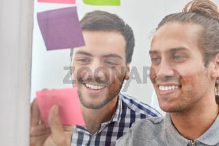 Zwei Studenten sammeln Ideen auf Zetteln