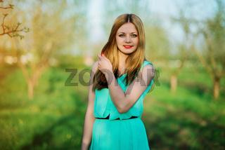 Woman in a beautiful long turqoise dress posing on a meadow in the fruit garden.