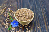 Flaxen brown seed in bowl with flower on dark board