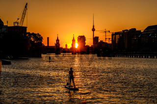 Oberbaum Bridge, Tv Tower , sunset sky and  paddle board , stand up paddler on river Spree in Berlin