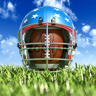 American football helmet over the oval ball, on the grass. Frontal Close up view.