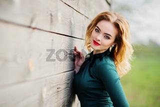 Yong elegance blonde girl at green dress background wooden texture.