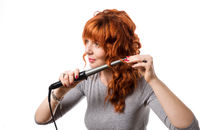 Portrait of beautiful woman curling red hair using curling iron, isolated on white