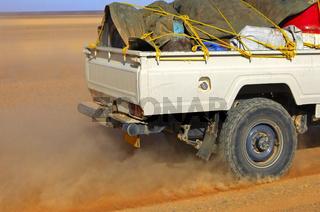 Jeep in schneller Fahrt auf einer Wüstenpiste