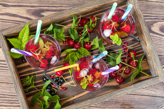 Three glasses of refreshing  drink flavored with fresh fruit in wooden box surrounded by fruit. Top view. Wooden background