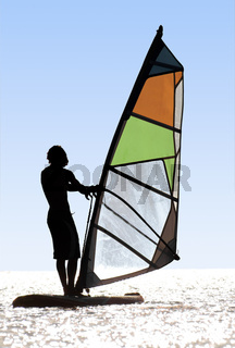 Silhouette of a windsurfer on waves of a bay