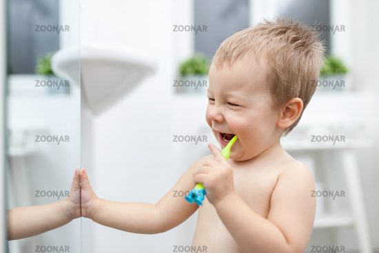 Adorable child learing how to brush his teeth in the bathroom