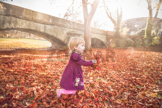 Child running with autumn leaves in hands