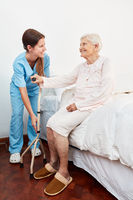 Junge Pflegekraft hilft behinderter Seniorin