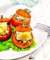 Tomatoes stuffed with meat on lettuce in plate on light board