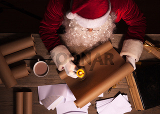 Santa Claus sitting at the table in his room and reading Christmas letter or wish list