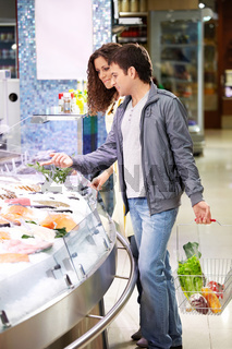 Young couple at a shelf with seafood in shop