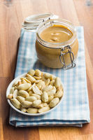 Peanut butter in jar and peanuts.