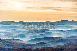 Ranges of blue mountains at sunset