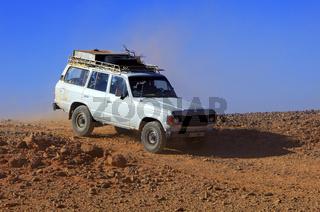 Jeep fährt auf steinige Schotterpiste durch die Wüste